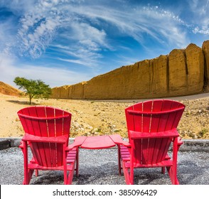 Two convenient red chaise lounges connected by small table stand for tourists. Walking route on  picturesque Black canyon