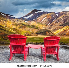 Two convenient red chaise lounges connected by small table stand for tourists.  Travel to Iceland in the July. Multi-colored mountains from mineral rhyolite are lit with sun
