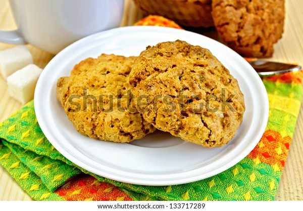 Two cookies on a white plate, spoon, sugar, cup, basket weaving, napkin on a wooden board