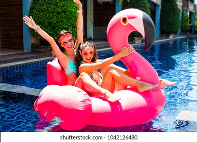 Two cool sexy girls in bright bathing suits and sunglasses are having fun in the pool floating on a large inflatable pink flamingo in a hotel on summer . The concept of summer leisure freedom