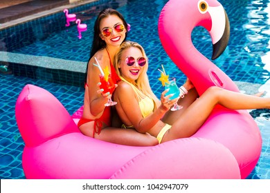 Two cool sexy girls in bright bathing suits and sunglasses are having fun in the pool floating on a large inflatable pink flamingo in a hotel on summer vacation. The concept of summer leisure