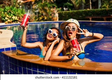 Two cool trendy beautiful funny happy sexy tanned girl swimming in the pool with a cocktail, sunglasses, cap, colorful swimwear, carefree day party, cheeky hippie.