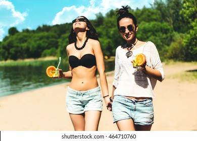 Two cool trendy hipster twin girls with cocktails at the beach enjoying vacation on a tropical island, perfect tanned body, healthy skin, sexy stylish casual wear, bikini, brunette twins in sunglasses