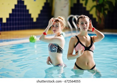Two cool young girls wearing bikini pose in the pool in the water park.