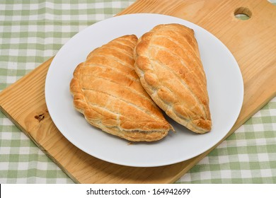 two Cornish Pasties on a plate in a cafe setting