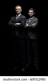 Two corporate business colleagues with arms crossed