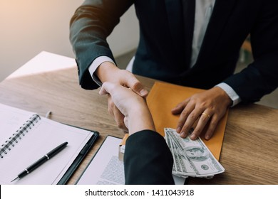 Two corporate businessmen shaking hands while one man places money on document in office room with corruption concept.