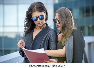 Two corporate women reviewing documents and discussing figures outside their workplace