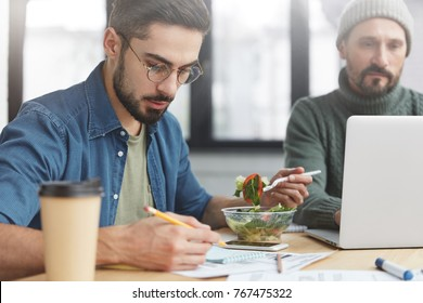 Two corporative workers work together at workplace: mature man keyboards on laptop and his companion writes attentively notes, eats fresh salad and drink coffee, have no time for going in cafe
