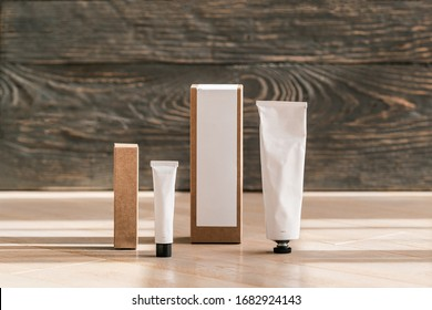 Two cosmetic white tubes and craft paper boxes on wooden table. Brand package layout. Closeup, copyspace for text