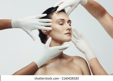 Two cosmetologists touching and examining facial skin of a female. Woman face being checked beauticians hands in studio.