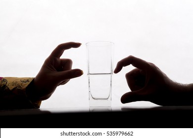 two couple are showing half full and half empty side of water glass with their fingers