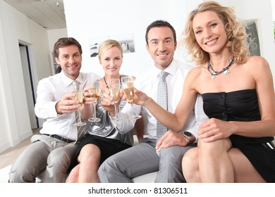 Two couple sitting holding up champagne glasses