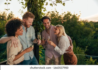 Two couples celebrating with drinks at the terrace party