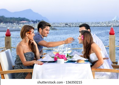 Two couples celebrating at the sea seated at a table at an open-air waterfront restaurant enjoying glasses of cold white wine as they wait for their meal