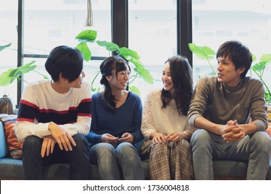 Two couples chatting on the sofa
