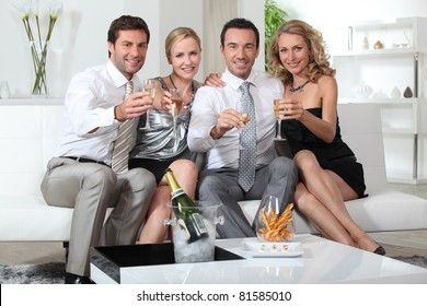 Two couples drinking champagne at home