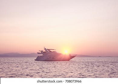 Two couples enjoying pink romantic sunset on private modern luxury yacht anchored at Mediterranean sea - luxury holidays and travel concept