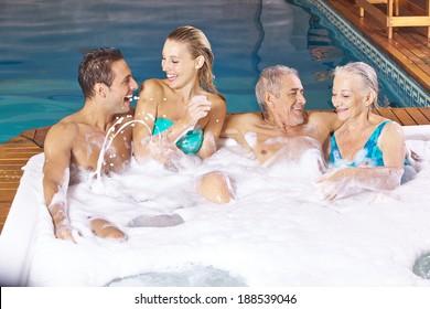 Two couples having fun in whirlpool with foam bubble bath