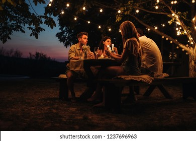 Two couples having a romantic dinner outdoors