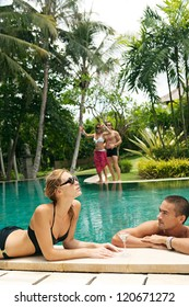 Two couples lounging and having fun by the edge of a swimming pool in a tropical destination hotel spa garden while on vacations.