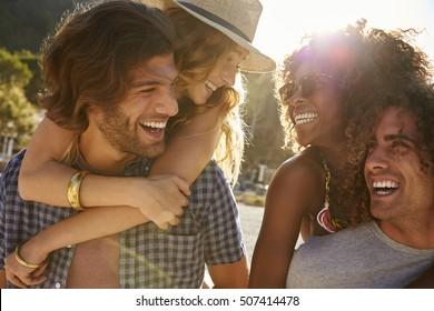 Two couples piggybacking at the beach, looking at each other