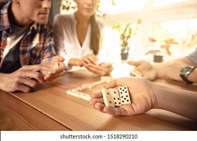 Two couples are playing dominoes while sitting in the the living room near the window.