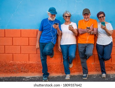Two couples of senior brothers and wifes looking at smart phone smiling against a colored wall - four happy people using tech and social - active retirement concept