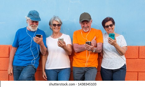 Two couples of senior people standing against an orange and blue wall smiling and looking at the mobile phone using earphones. Casual clothing and relaxed faces