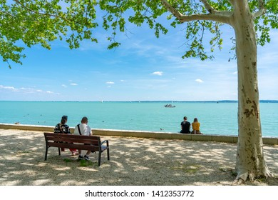 Two Couples sitting in the bench facing to the lake Balaton