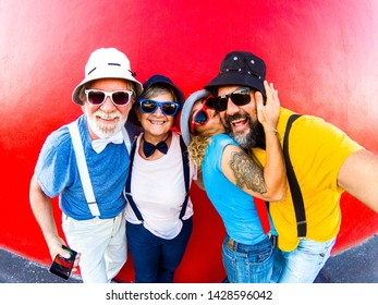 Two couples take selfie with a red wall behind. Dresses full of color, with bow tie and suspenders, smiling and kissing. Emotion and love for four funny peoples