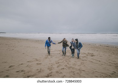 Two couples talk and laugh together whilst walking along a beach in winter.