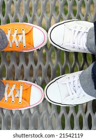 Two couples of teenagers feet in sneakers standing on grid face to face