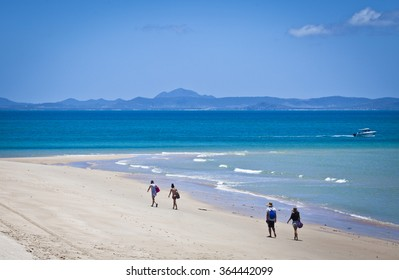 Two couples walk on an ideal beach on Keppel Island, Queensland, Australia. Sun soaked sand beside turquoise ocean at the start of the Great Barrier Reef.