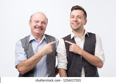 Two coworkers of different age pointing finger each other and looking at camera with happy face. He is my buddy concept