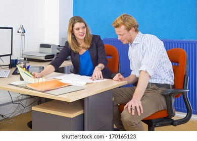 Two coworkers, forming a project team, discussing a design brief and some technical drawings, spred out over a desk in an office
