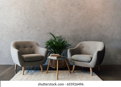 Two cozy grey armchairs standing on white carpet in empty room