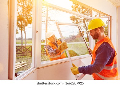 Two craftsmen from a glazier assemble windows in the new house