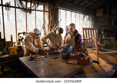 Two craftsmen and their apprentices in their craft workshops work on metal parts to assemble them on a wooden chair.