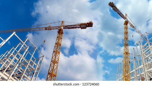 Two cranes build industrial buildings on a background beautiful sky