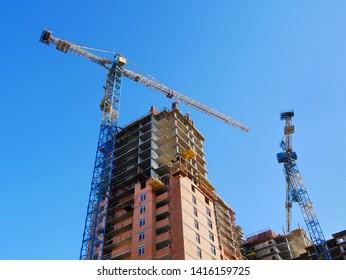Two cranes near building. Concrete building under construction. Construction site background.