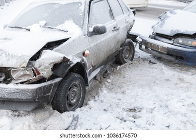 Two crashed cars in accident on winter road with snow