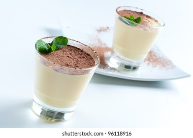 Two creamy vanilla desserts with cocoa and mint leaf