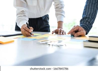 Zwei kreative Geschäftsleute, die sich treffen und planen, nutzen Post es klebrige Notizen auf dem Schreibtisch, um Ideen, Analyse-Datendiagramm und Graphen mit Teamwork Strategie Brainstorming im Büro zu teilen.