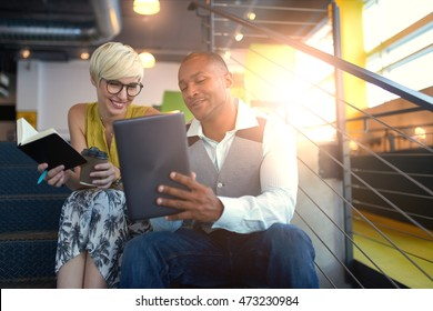 Two creative millennial small business owners working on social media strategy using a digital tablet while sitting in staircase