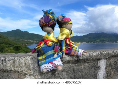 Two Creole Dolls sitting in the stone wall against the Caribbean sea and island view.