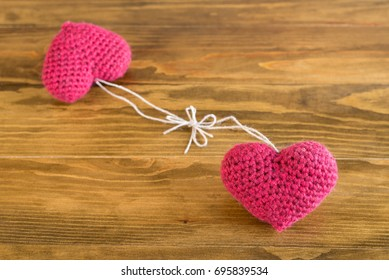 Two crocheted hearts on a wooden table