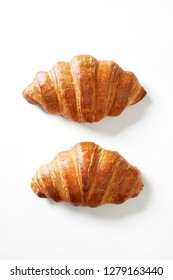 Two croissants isolated on a white background viewed from above. Top view.