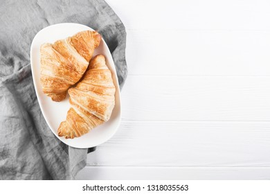 Two croissants on oval white plate. Grey napkin and white wooden table on background.