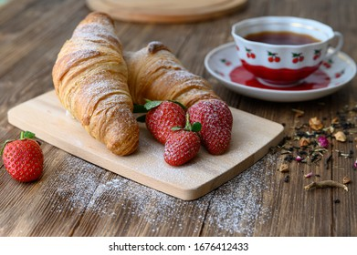 Two croissants on a wooden cutting board with strawberries and a cup of tea
